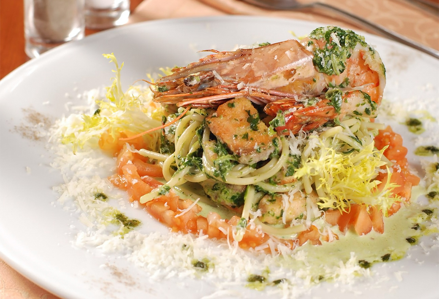 Спагетти с королевской креветкой и лососем под соусом из шпината на подушке из свежих томатов